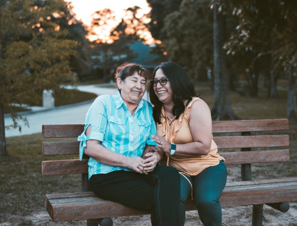 two women laughing on a park bench