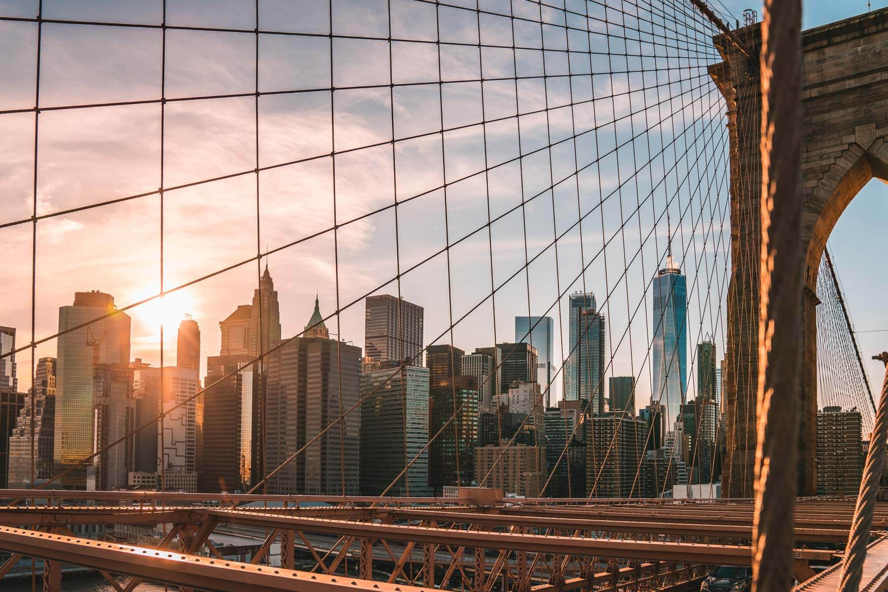 the new york skyline through the lines of the bridge during sunset