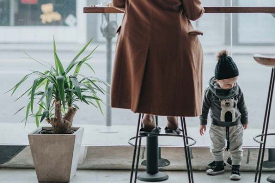 a mother in a long trench coat with her toddler son