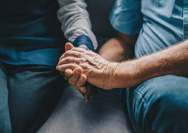 a young man softly holding an elder man's hand for comfort